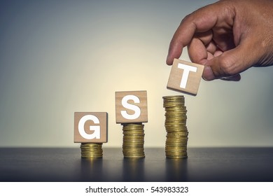 GST Concept with wooden block on a stacked of coins