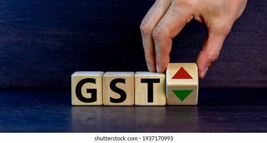 GST, goods and services tax symbol. Businessman holds a cube with up and down icon. Word 'GST'. Beautiful grey background. Copy space. Business and growth of GST, goods and services tax concept.