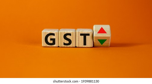 GST, goods and services tax symbol. Wooden cubes with up and down icon. Word 'GST'. Beautiful orange background. Copy space. Business and growth of GST, goods and services tax concept.
