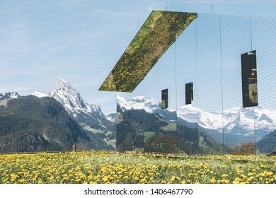 GSTAAD - MAY 23, 2019: The Swiss Alps reflected on Mirage Gstaad by Doug Aitken