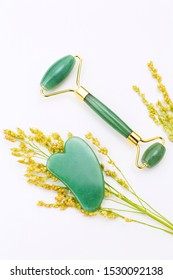 Gua sha stone and jade roller still life arranged with golden wildflowers on white surface / natural holistic beauty concept