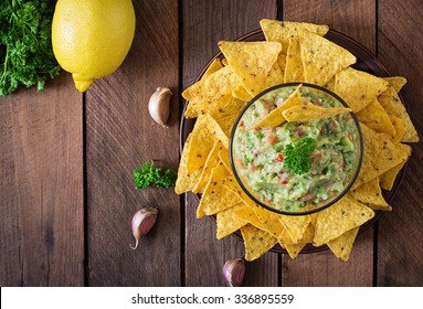 Guacamole avocado, lime, tomato, onion and cilantro, served with nachos - Traditional Mexican snack. Top view