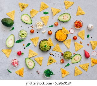 Guacamole bowl with fresh ingredients and tortilla chips on a vintage table. Top view. Flat lay