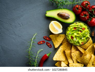 Guacamole bowl with ingredients and tortilla chips on a stone table. Top view image. Copyspace for your text