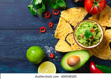 Guacamole bowl with ingredients and tortilla chips on a blue painted wooden table. Top view