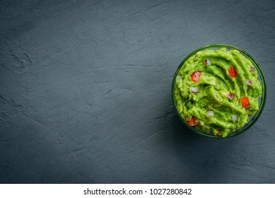 Guacamole bowl on a stone table. Top view image. Copyspace for your text