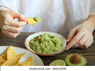 Guacamole and corn chips. the hand of a girl who eats Guacamole