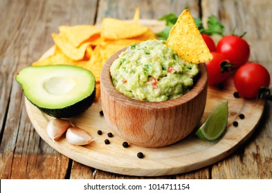 Guacamole with corn chips and ingredients to prepare it on a wood background. toning. selective focus