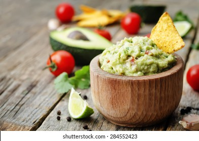 guacamole with corn chips on a dark wood background. the toning. selective focus