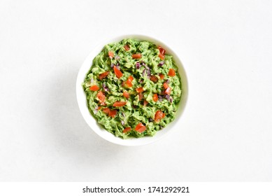 Guacamole dip in bowl over white stone background with free text space. Healthy avocado spread. Top view, flat lay