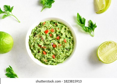 Guacamole dip in bowl over white stone background. Healthy avocado spread. Top view, flat lay