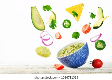 Guacamole with flying corn chips and ingredients to prepare it on a white background. toning. selective focus