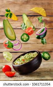 Guacamole with flying corn chips and ingredients to prepare it on a wood background. toning. selective focus