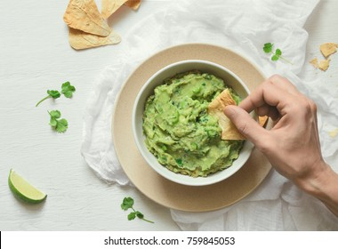 Guacamole freshly cooked and served in a bowl, overhead view on woman hand is picking some guacamole dip with pita chip