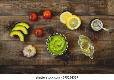 Guacamole and ingredients, avocado, lemon and olive oil. Top view