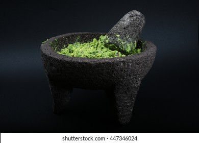 guacamole in a mexican molcajete with a chopping stone