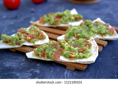 Guacamole, Mexican sauce or a snack from avocado and tomato on a dark gray concrete background. Served with wheat tortilla. Healhty eating concept.