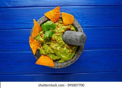 Guacamole with nachos avocado in Mexican molcajete on blue wood table