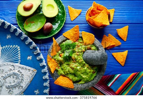 Guacamole with nachos avocado in Mexican molcajete and Sombrero hat