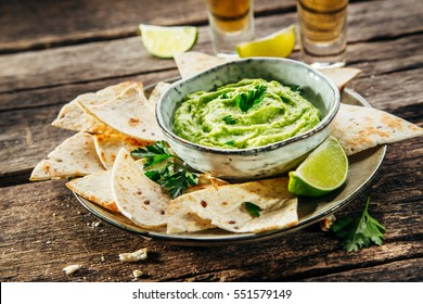 Guacamole with Nachos on plate. Mexican traditional food, Rustic style