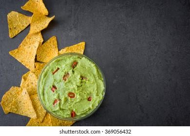 Guacamole and nachos on slate