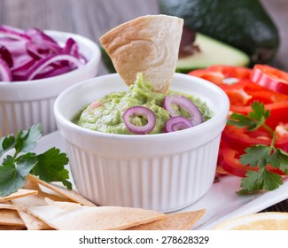 Guacamole in porcelain Bowl with mexican Tortilla Chips nachos and Ingredients