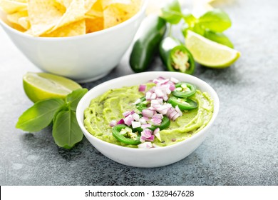 Guacamole with red onion and Jalapeno pepper in a white bowl with chips