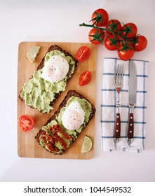 Guacamole sandwich with poached eggs, dry tomatoes, lime on a wooden board. Healthy vegetarian breakfast concept. Black bread, fresh cherry tomatoes. Top view.