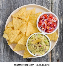 guacamole, tomato salsa and corn chips on a plate, top view, closeup