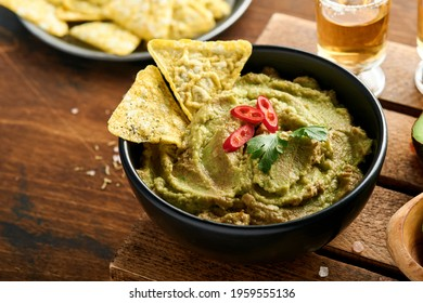 Guacamole. Traditional latinamerican Mexican dip sauce in a black bowl with avocado and ingredients and corn nachos. Avocado spread. Top view. Copy space.