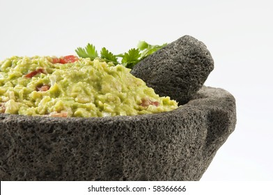 Guacamole traditionally prepared in a volcanic stone bowl called molcajete, close up view.