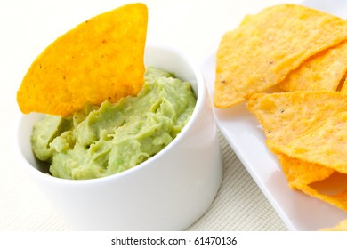 guacamole in white bowl with nachos