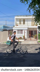 Guadalajara, Jalisco, Mexico; August 23 2019: Young male wearing work clothes riding bike while running errands on the street in urban setting, with green box