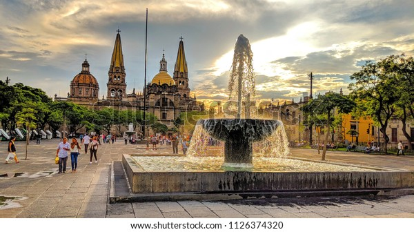 Guadalajara, Jalisco, Mexico - June 26, 2018: Visitors and locals enjoy a summer sunset in Liberation Square just outside the Guadalajara Cathedral.