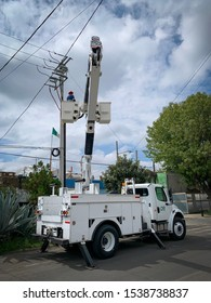 Guadalajara, Mexico - October 22 2019: Electrical post fire incident. Electrical company worker on crane truck bucket attend to an electrical post fire incident. Electrical maintenance