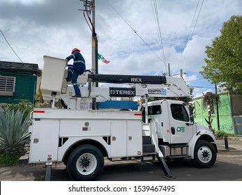 Guadalajara, Mexico - October 22 2019: Electrical post fire incident. Electrical company worker on crane truck bucket attend to electrical post fire incident. Electrical maintenance vehicle CFE logo