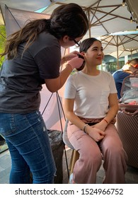Guadalajara, Mexico - October 6 2019: Young woman carefully pierces another woman's earlobe with gun at a street market. Pink and white scene. Open market. Piercing equipment
