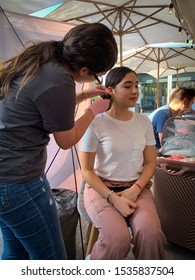 Guadalajara, Mexico - October 6 2019: Young woman carefully pierces another woman's earlobe with gun at a street market. Pink and white scene