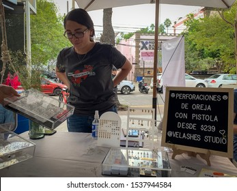 "Guadalajara, Mexico - October 6 2019: Female piercer  wearing top reading Don't Over Think it, stands by an ear piercing stand. Sign reading ""Ear piercings with gun, from $239"". Piercing business"