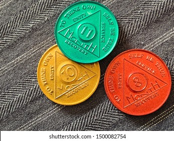 Guadalajara, Mexico - September 9 2019: AA Sobriety chips awarded abstaining from alcohol or other substance for for 8, 10 and 11 months. It is a token given to 12 step group members. Successful rehab