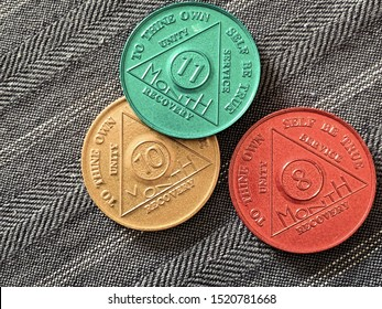 Guadalajara, Mexico - September 9 2019: AA Sobriety chips awarded from abstaining from alcohol or other substance for 8, 10, 11 months. It is a token given to 12 step group members. Successful rehab