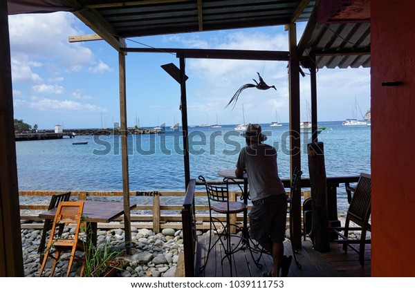 GUADELOUPE, CARIBBEAN, FRANCE - FEBRUARY 9, 2018: Man stands outdoor restaurant by Caribbean sea Guadeloupe,  Deshaies.