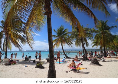 GUADELOUPE, FRANCE - DECEMBER 8, 2019: People spend beach vacation in Sainte Anne on Guadeloupe island. Guadeloupe has 650,000 annual visitors.