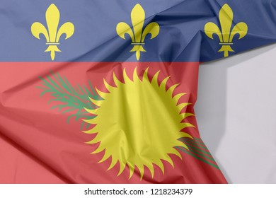 Guadeloupe Local fabric flag crepe and crease with white space, red field with yellow sun and green sugar cane, and a blue stripe with yellow fleurs-de-lis on the top.