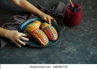 Guaguas de pan y colada morada with child hands, Figuras de pan ecuatorianas for Ecuador's Día de los Difuntos or Day of the Deceased          - Shutterstock ID 1484487719