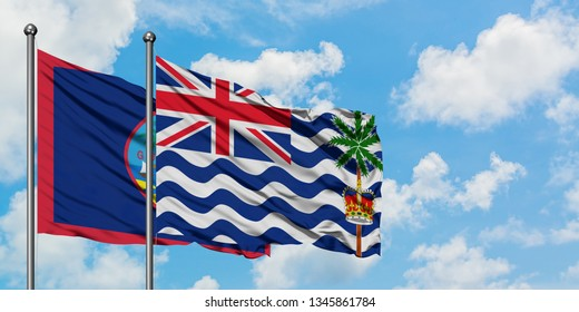 Guam and British Indian Ocean Territory flag waving in the wind against white cloudy blue sky together. Diplomacy concept, international relations.