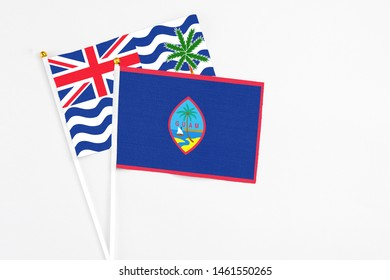 Guam and British Indian Ocean Territory stick flags on white background. High quality fabric, miniature national flag. Peaceful global concept.White floor for copy space.