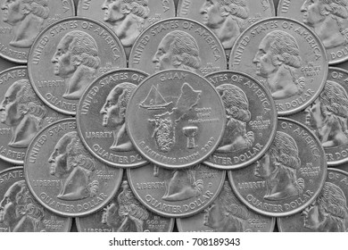 Guam Island and coins of USA. Pile of the US quarter coins with George Washington and on the top a quarter of Guam Island.