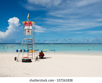 GUAM, USA - NOVEMBER 11, 2016: Tumon Beach in Guam, USA. Tourists are enjoying water sports such as swimming or snorkeling in the sea while a lifeguard is watching the people.