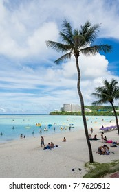 GUAM, USA - NOVEMBER 11, 2016: Tumon Beach in Guam, USA. Tourists are resting on the beach or are enjoying water sports. Tumon beach is one of the most famous tourist attractions in Guam.